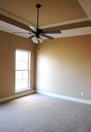 the master bedroom has a tray ceiling and double crown molding