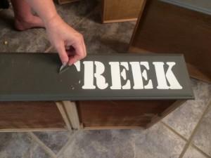 dresser pulling stencil letter off
